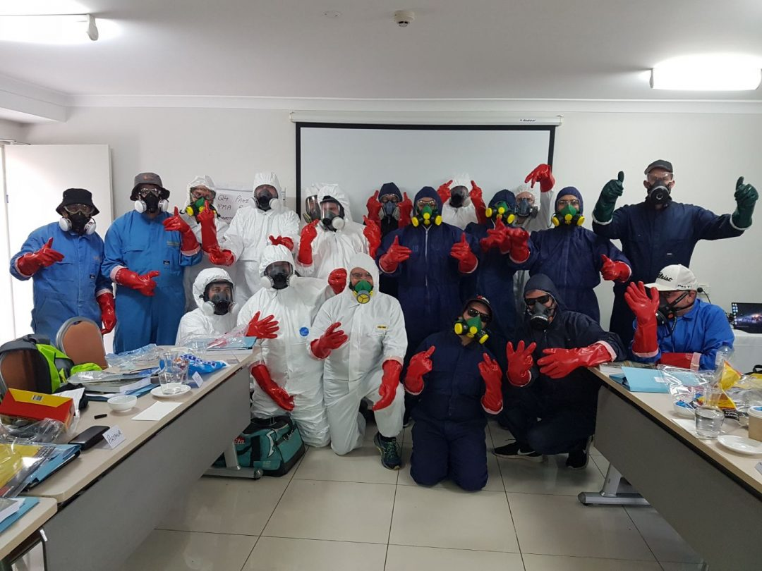 Pest management course students in classroom with protective gear